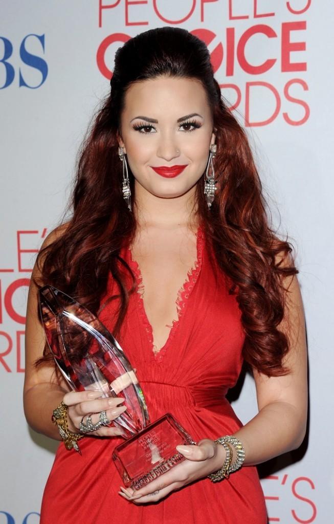Banane sur le haut, cheveux rouge et lipstick bien rouge, Demi, joue la carte de la féminité