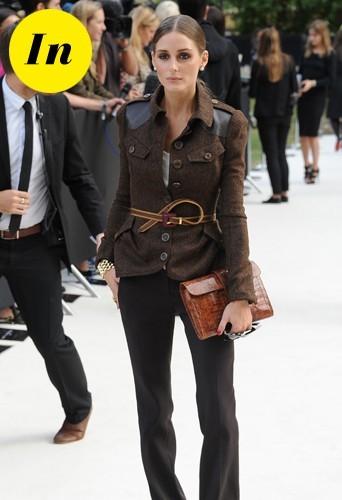 Olivia porte une veste ceinturée Burberry et une pochette Hermès.