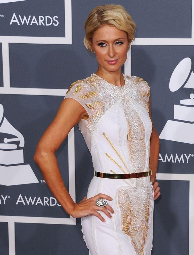 Paris Hilton marque sa taille avec une ceinture dorée, fine et élégante.