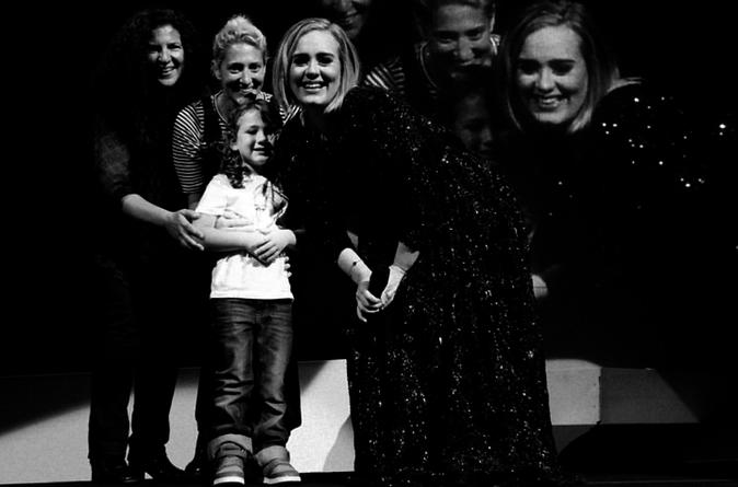 Adele sur scène avec des fans pendant son concert